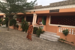 Dr. Helen in front of the Good Samaritan School run by Pastor Vincent which educates 200 students. The far left of this building is the clinic.